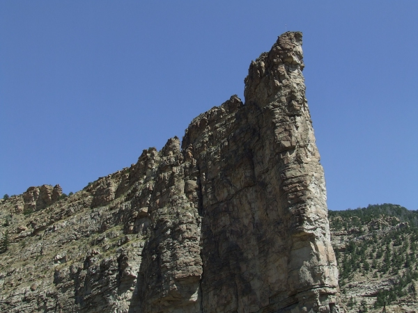 A pinnacle of rock towers up, surrounded by piñon.