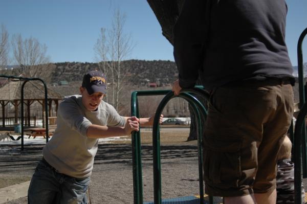 Eli pushes a merry-go-round